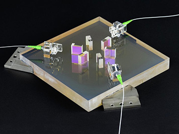 photo of optical bench with lasers coming through fiber