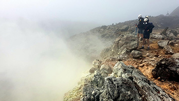 photo of researcher at edge of volcano