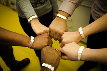 six arms of different skin tones, each wearing UV wristband